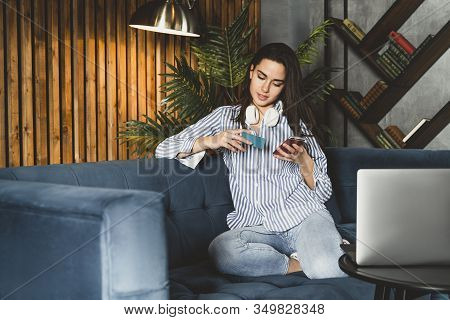 Girl Relaxing On Sofa Using Her Smartphone For Online Shopping. Young Female Paying For Purchased Go