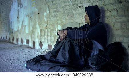 Homeless Teenager Watching People Passing By Indifferently, Abandoned By Society