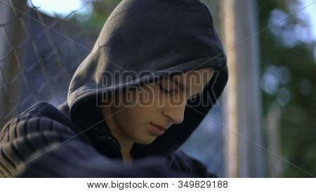 Teen Guy Feeling Himself Helpless, Upset With Bullying, Hiding On Backyard