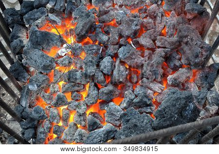 Black Coal Heated On The Street Bin Cold Winter