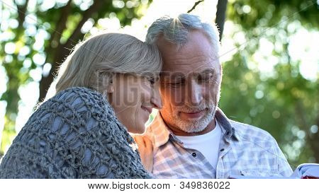 Mature Couple Watching Family Album Sitting On Bench In Cozy Garden, Nostalgia