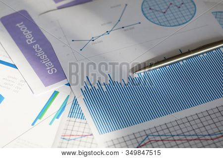 Inscription On Documents, Statistical Report. On Table Are Papers With Graphs And Charts That Help T