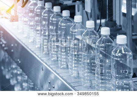 The Pet Bottles In The Rail On The Conveyor Belt For Filling Process In The Drinking Water Factory.