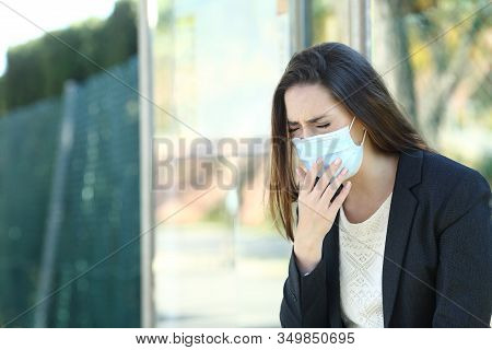 Infected Woman Wearing A Protective Mask Coughing Waiting In A Bus Stop