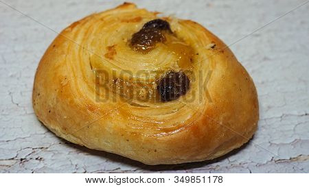 Traditional Raisin Swirl, Pain Aux Raisins From France. Closeup View On White Wooden Background