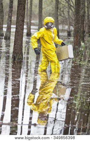 Technician in professional uniform with silver suitcase  in contaminated  floods area - front view