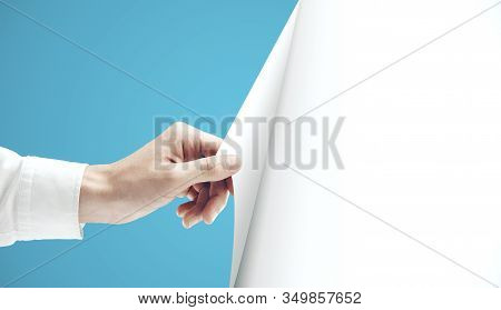 Man Hand Turning Blue Page Of Blank White Paper. Occupation And Worker Concept.