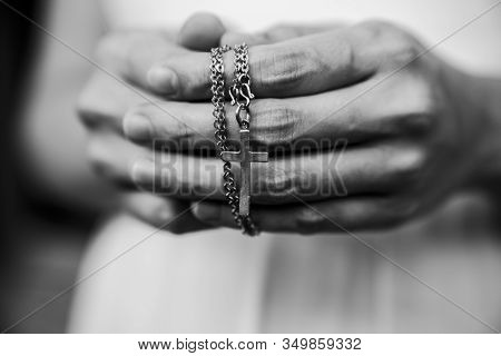 Black And White Of Woman Hands Praying Holding A Beads Rosary With Jesus Christ In The Cross Or Cruc