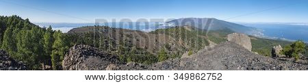 Panoramatic View Of Volcanic Landscape With Lush Green Pine Trees, Colorful Volcanoes And White Clou