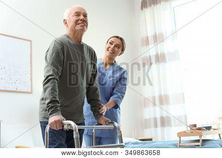 Care Worker Helping Elderly Man With Walker In Geriatric Hospice