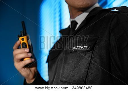 Professional Security Guard With Portable Radio Set Near Window In Dark Room, Closeup