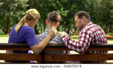 Caring Mother And Dad Supporting Sad Teen Son Sitting On Bench In Park, Crisis