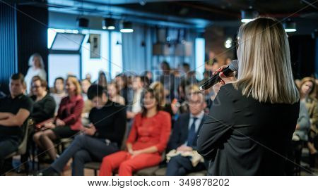 Female presenter speaks to audiences at seminar