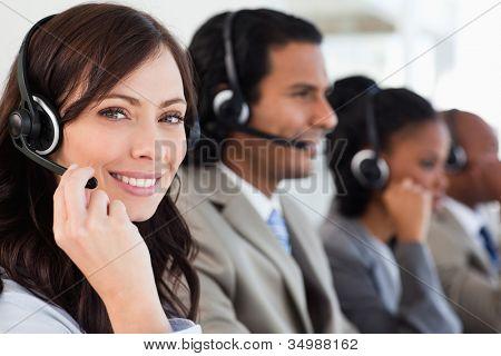 Lachende werknemers doet haar werk met een headset tijdens het kijken naar de camera