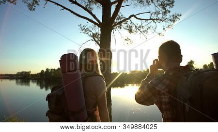 Backpackers Taking Photo Of Gorgeous Scape, Beautiful River And Sunset View