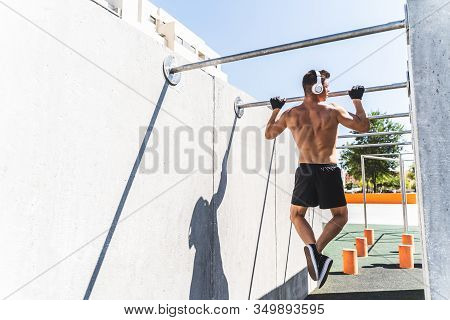 Young Man Doing Training Calisthenics On Pull-ups Bar Outdoors.