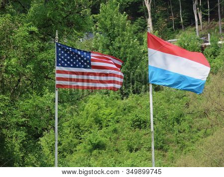 American And Luxembourg National Flags Waving In Wind Together In Weilerbach, Luxembourg, In Honour
