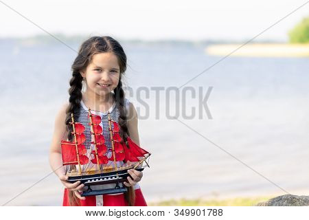 Portrait Of A Happy Little Girl By The Lake. In Her Hands She Holds A Toy Sailboat With Scarlet Sail