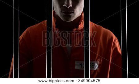 Criminal In Orange Uniform Behind Prison Bars, Serving Life Sentence For Murder