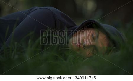 Homeless Male Sleeping On Grass In Park, Poverty And Social Issues Concept