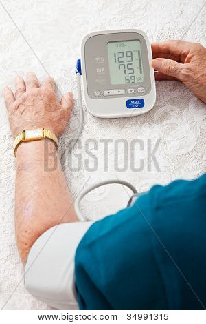 Closeup of a senior man's arm hooked up to a home blood pressure machine, showing his results.