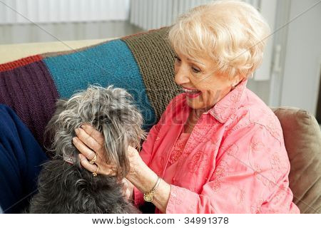 Beautiful senior lady pats her adorable mixed breed dog.