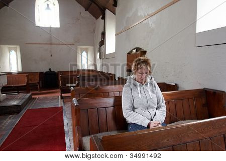 A Woman Sitting In An Empty Church Praying