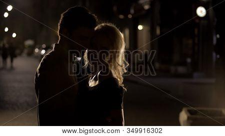 Blond Female Teasing And Cuddling Boyfriend In The Night Street, Silhouettes
