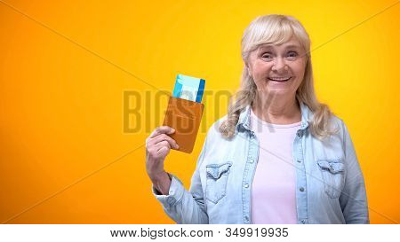 Happy Retiree Lady Showing Passport And Tickets, Travel Agency Advertisement