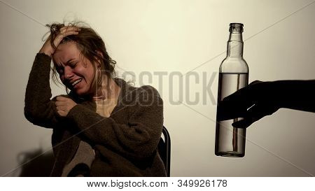 Alcoholic Woman Suffering Strong Withdrawal, Male Hand Holding Bottle Of Vodka