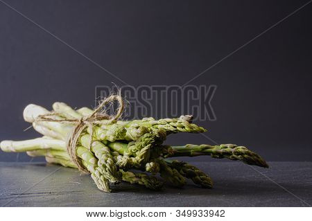 Close-up Of A Bundle  Of Bright Green Asparagus Tied With Twine On A Gray Slate Surface With Copy Sp