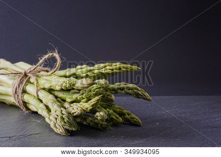 Close-up View Of A Bundle Of Spring Asparagus Tied With Twine On A Gray Slate Surface With Copy Spac
