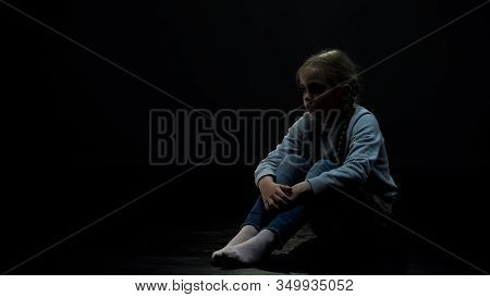 Upset Little Girl Sitting In Dark Room Alone, Fear And Problems, Orphan Kid