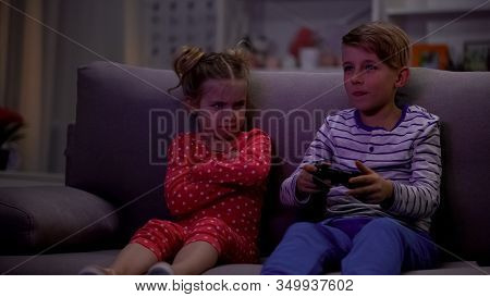 Brother Playing Video Game Using Joystick, Sister Taking Offence For Loosing