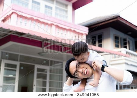 Asian Father Giving A Piggyback Ride For Little Son In Front Of The House. Dad And Child Enjoying Wa