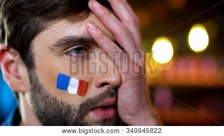 Anxious French Fan With Painted Flag On Cheek Making Facepalm, Disappointment