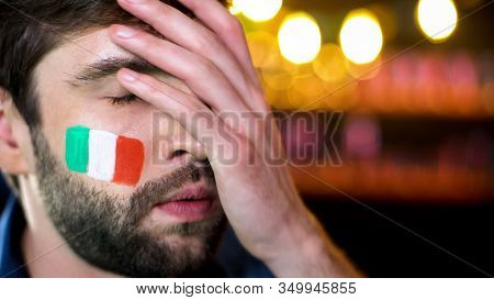 Nervous Bearded Male Fan With Italian Flag On Cheek Making Facepalm, Team Losing