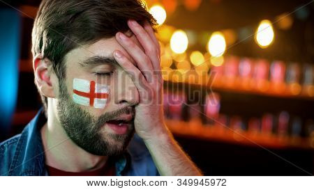 Displeased Male Football Fan With English Flag On Cheek Making Facepalm Gesture