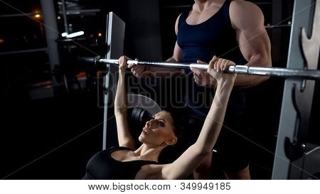 Female Doing Barbell Bench Press In Gym, Exercise Under Trainer Supervision