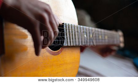 The Guy Plays The Guitar, Yellow Wooden Musical Instrument. Man Iterates Over The Strings Of A Acous