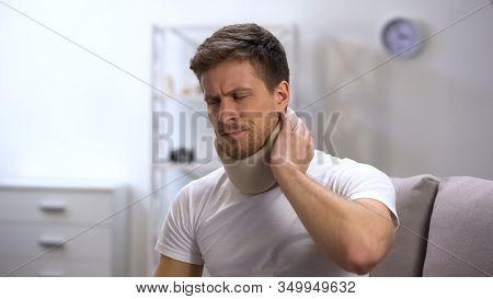 Upset Man In Foam Cervical Collar Suffering Neck Pain, Rehabilitation Center