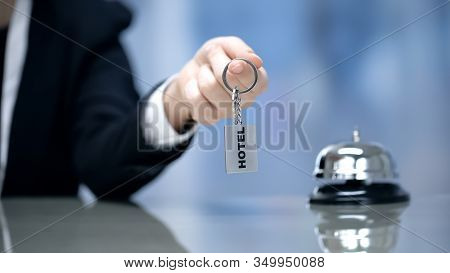 Female Hand Holding Hotel Room Keys Near Bell On Reception, Hospitality Services