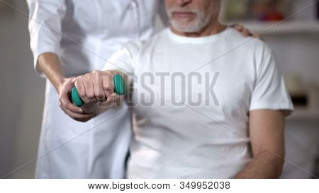 Nurse Helping Pensioner To Lift Dumbbell, Rehabilitation Center After Insult
