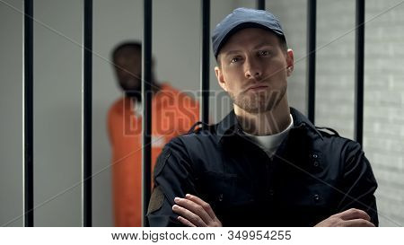 Prison Warden Looking To Camera Standing Near Cell With Imprisoned Afro-american