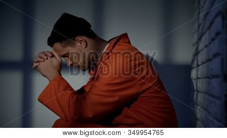 Caucasian Imprisoned Male Praying In Cell, Feeling Guilty And Asking For Mercy