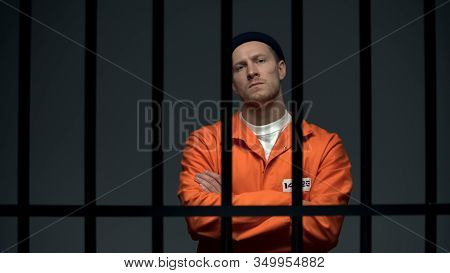 Imprisoned Dangerous Male Criminal Crossing Hands On Chest, Looking Directly