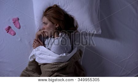 Sad Lady Crying Lying In Bed And Looking At Baby Socks Near Pillow, Miscarriage