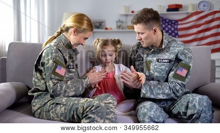 Cheerful Us Military Couple Playing Pat-a-cake With Little Daughter At Home