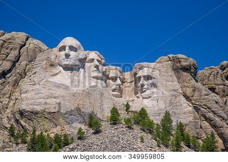 Mount Rushmore With Blue Sky And Green Trees.