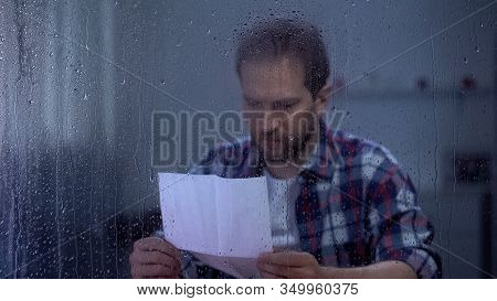 Sad Man Reading Letter Behind Rainy Window, Bank Credit Payment Overdue, Poverty